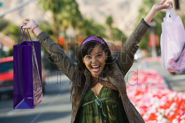 teenage girl (16-17) raising shopping bags in street (portrait) stock photo