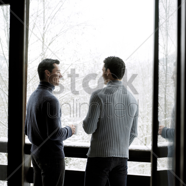 two men enjoying hot drinks while talking in the chalet stock photo