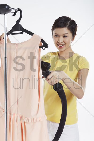 woman ironing a dress stock photo