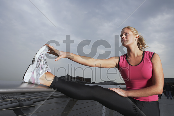 woman stretching on foot bridge low angle view stock photo