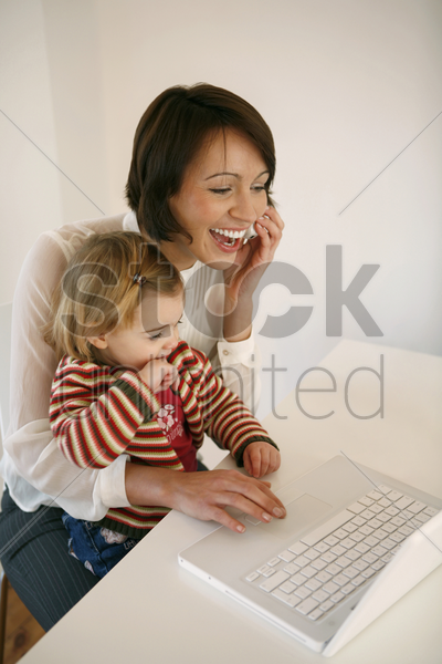 woman talking on the phone and using laptop while taking care of her daughter stock photo
