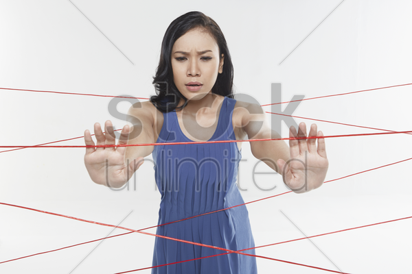 woman trapped in between tangled wires stock photo