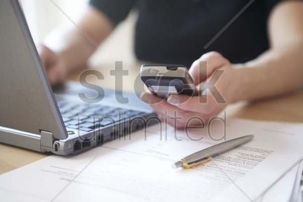 woman using laptop and mobile phone close up stock photo