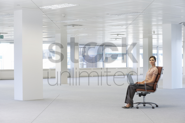woman using laptop in empty office space stock photo