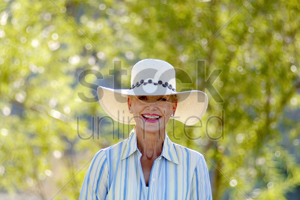 woman with hat smiling at the camera stock photo