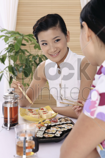 young women enjoying japanese cuisine stock photo