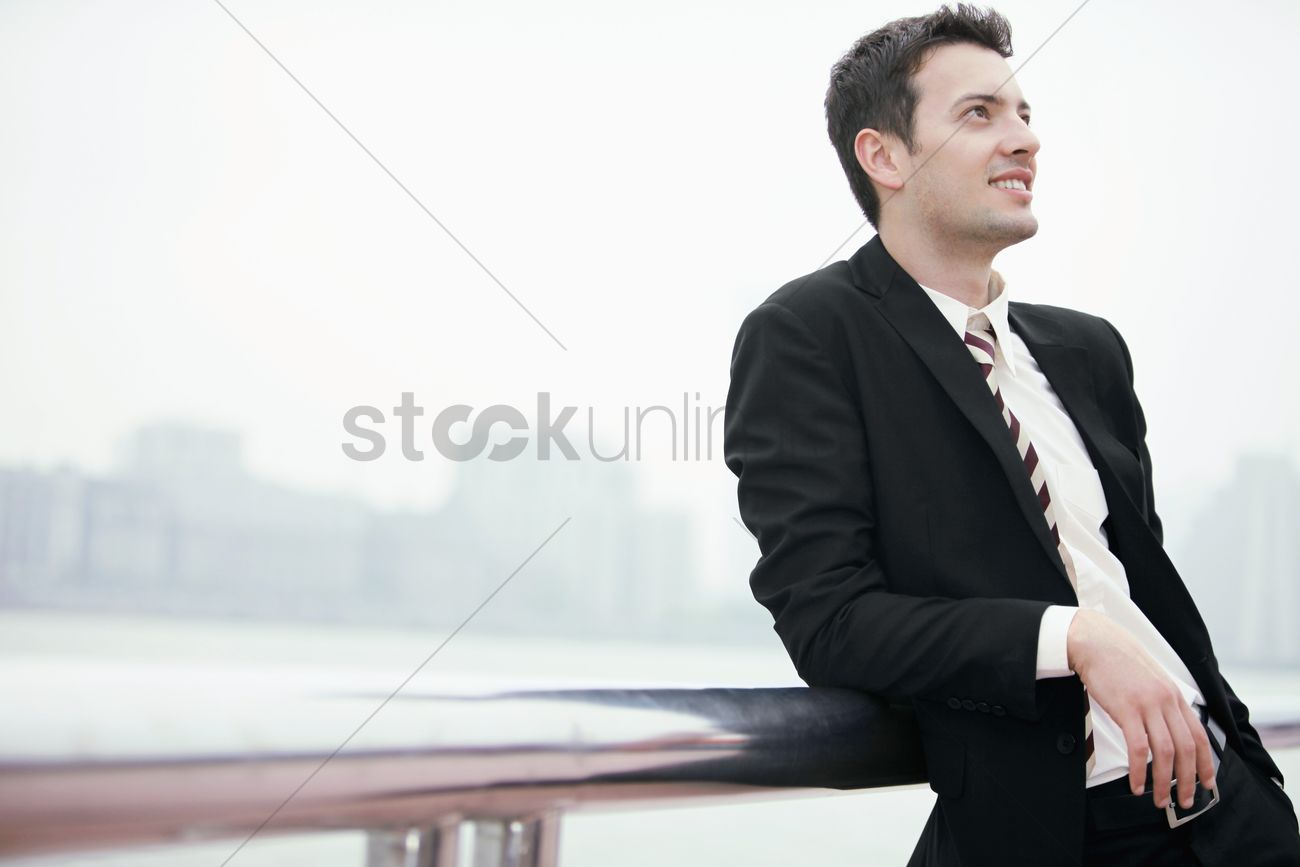businessman smiling and leaning on railing stock photo 1857900