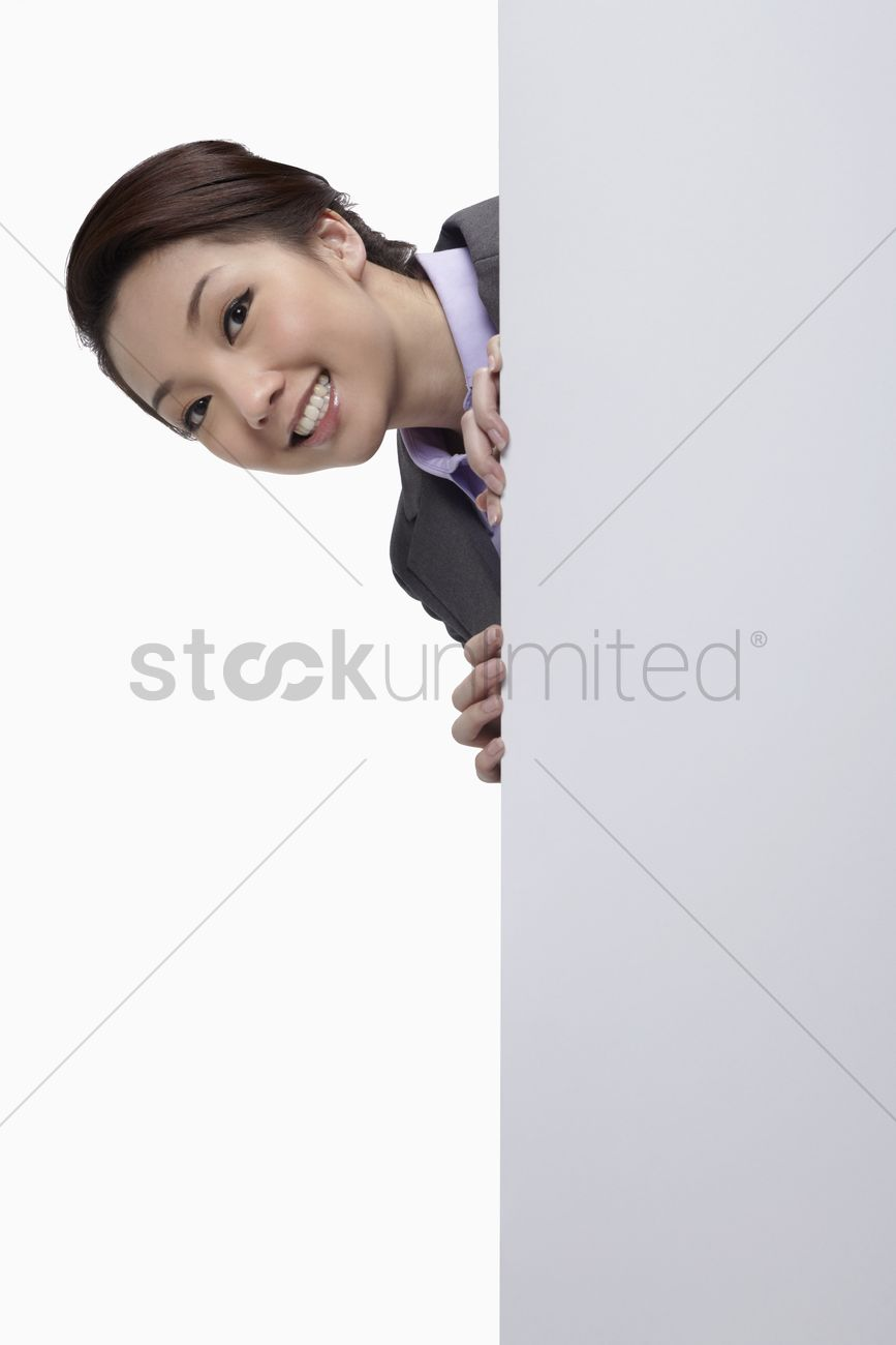 businesswoman hiding behind blank placard head popping out stock