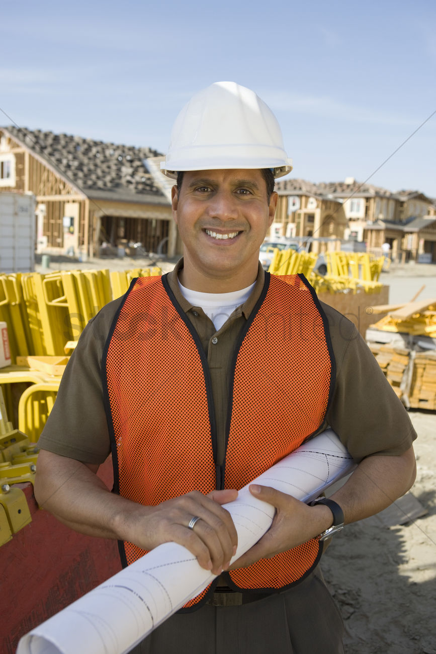 Construction worker standing on construction site and holding construction worker standing on construction site and holding blueprints stock photo malvernweather Gallery