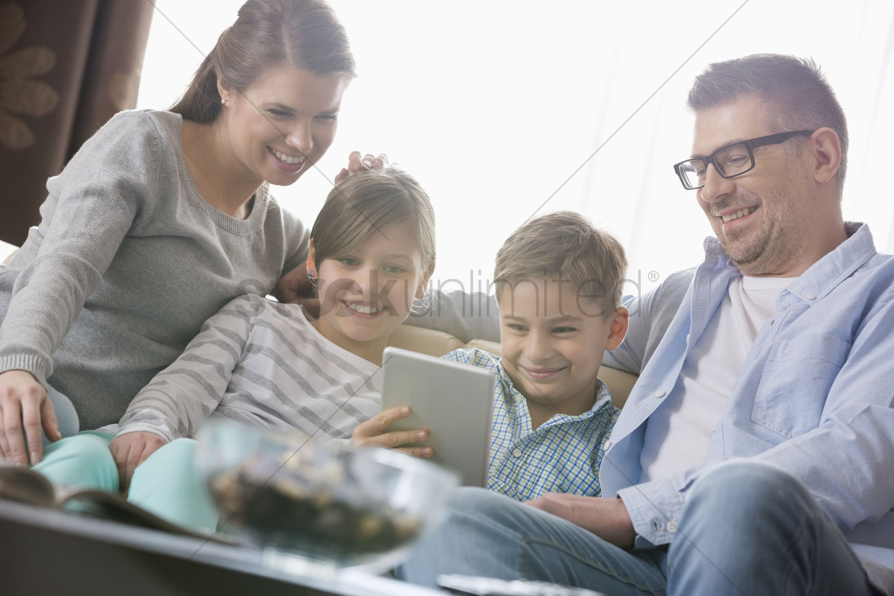 Happy family using digital tablet together in living room ...