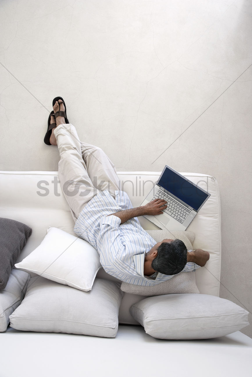 Man Using Laptop Sitting On Sofa In Living Room View From Above