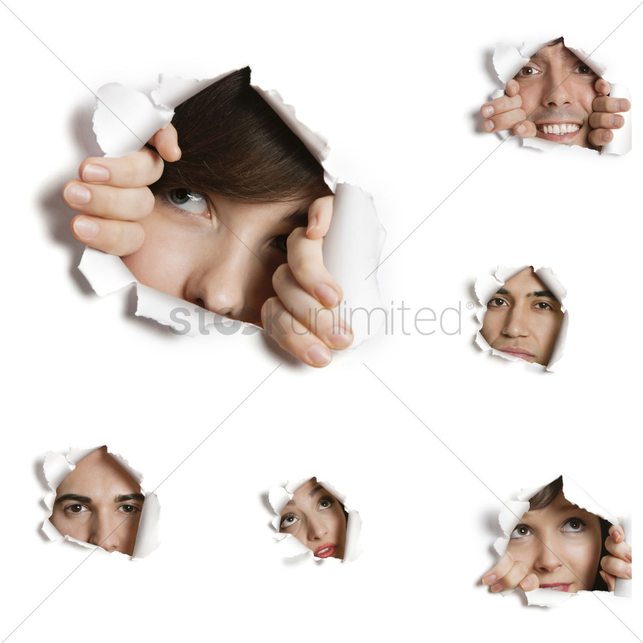 Multiethnic people looking through ripped paper holes Stock Photo