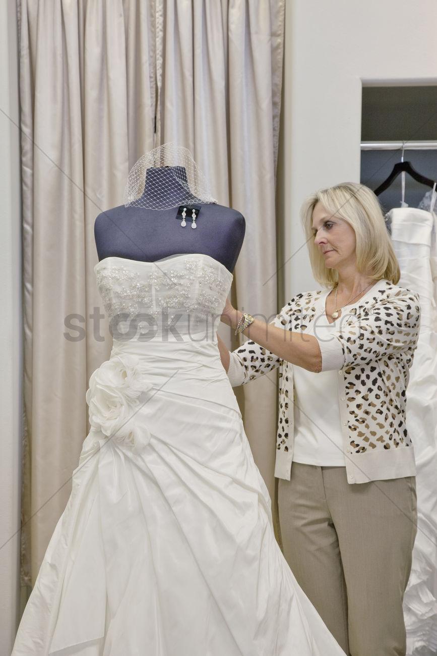 Senior Female Owner Adjusting Wedding Dress On Mannequin In Bridal Stock Photo