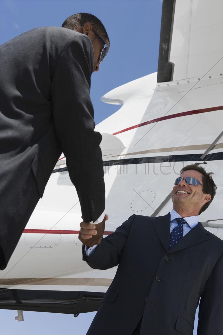 Two mid-adult businessman shaking hands in front of airplane low