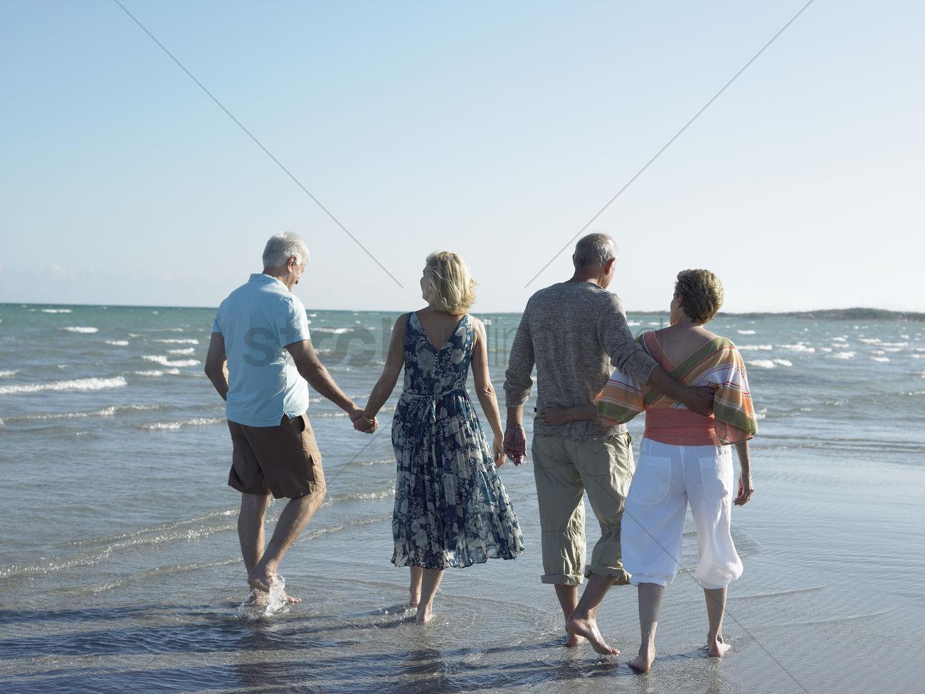 Two Senior Couples Walking On Beach Back View Stock Photo 1884948