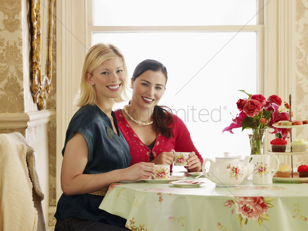 two young women sitting at dining table drinking tea portrait stock photo b323af23d