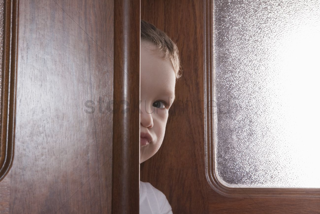 Young Boy Peeks Round Wooden Door Frame Stock Photo