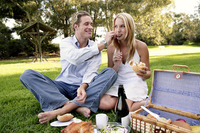 A guy feeding his girlfriend while picnicking on the field