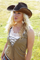 A woman in cowboy hat standing alone on the prairie