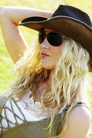 A woman with cowboy hat and sunglass lying on the grass