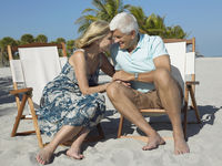 Affectionate senior couple on sunloungers on beach holding hands