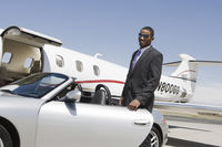 African-american businessman opening door of convertible on landing strip