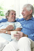 An old couple sitting together on the couch holding cups