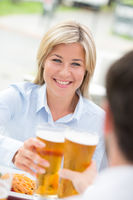 Beautiful businesswoman toasting beer glass with male colleague at restaurant