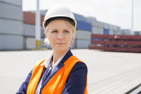 Beautiful female engineer looking away in shipping yard