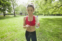 Beautiful fit woman listening to music through cell phone in park