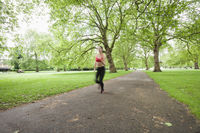 Blurred motion of woman jogging in park