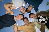 Boy  13-15  with brothers and father in huddle view from below
