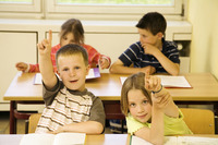 Boy and girl raising their hands to answer question