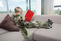 Boy in dinosaur costume reading story book on sofa at home