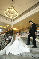 Bride and groom posing indoors on the stairway