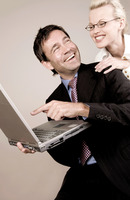 Business people laughing while using laptop