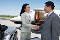 Business people standing near sports car and private airplane shaking hands side view