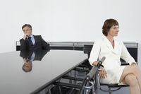 Business woman with back to business man at conference table