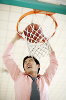 Businessman dunking basketball