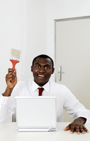 Businessman holding a paint brush while sitting in front of the laptop