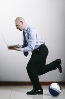 Businessman playing football while using laptop