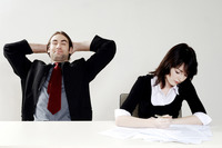 Popular : Businessman relaxing while his colleague is doing her work