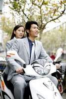 Businessman riding on a scooter with businesswoman sitting behind him