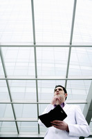Popular : Businessman thinking while holding an organizer