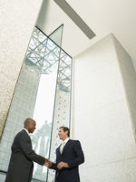 Businessmen shaking hands in office building  low angle view