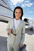 Businesswoman beside an airplane holding sunglasses low angle view