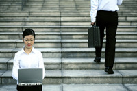 Businesswoman sitting at the staircase using laptop