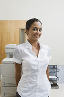 Businesswoman standing by photocopier
