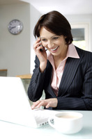 Businesswoman talking on the phone while using laptop