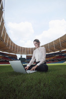 Businesswoman using laptop in an empty stadium
